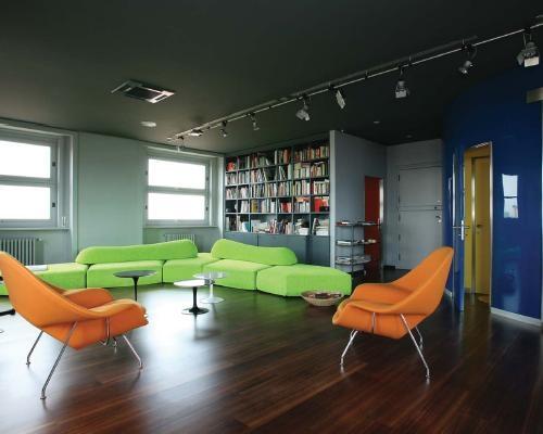 L'ampio open space della casa arredato con le womb chairs e i tavolini della serie tulip tutti di Saarinen e il divano on the rocks di Edra