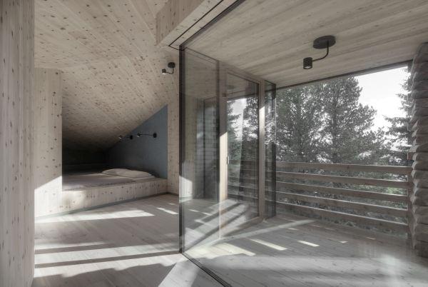 Una camera dello Chalet Odles tutta in legno e con grande vetrata