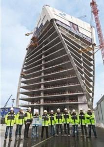 I responsabili del cantiere della Renaissance Construction posano orgogliosi davanti all'Evolution Tower, elegante grattacielo che si avvita su sé stesso.