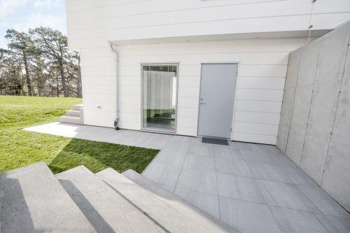 Pavimentazione esterna del nuovo progetto residenziale in Svezia, realizzata con la collezione Back di Ceramiche Keope, nella finitura Naturale, color Grey, cm 60x60. Grazie al formato e la raffinata nuance, Back contribuisce a definire con rigore ed eleganza gli spazi interni, donando un design minimalista ed estremamente moderno