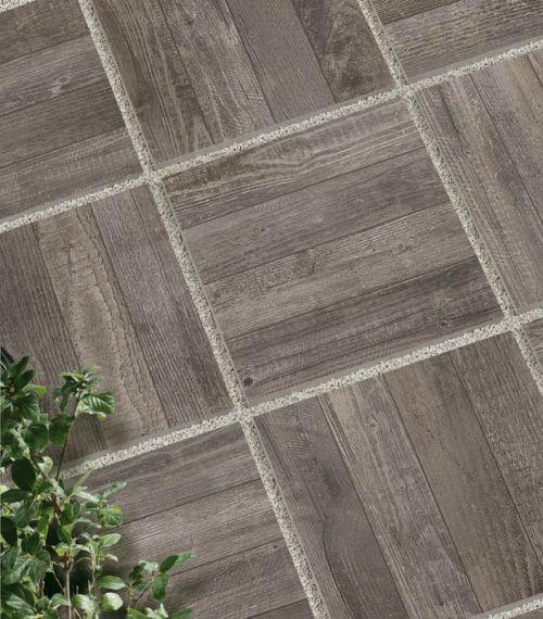 Particolare di K2 posato a secco su ghiaia, qui proposta nell'elegante effetto legno vissuto di Soul, nella versione Grey. Caratterizzata da uno spessore di 20 mm, K2 può essere posata a secco anche su sabbia e fondi erbosi, oltre che con la tradizionale posa a colla su massetto o su pavimento sopraelevato.