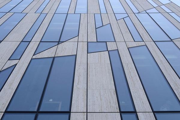L'eterogenea facciata nasce dalla una griglia modulare caratterizzata dal diverso ordine di elementi complanari di grandezza differente, composti da travertino e vetro.
