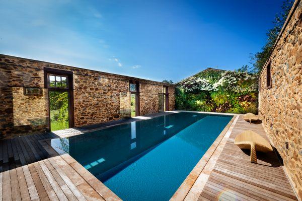PISCINE CASTIGLIONE firma il progetto di una piscina realizzata in un vecchio fienile privo di tetto e in disuso