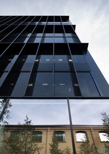 Gucci Hub, la  facciata in vetro scandita da una trama di brisoleil in metallo scuro.