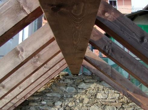 In questa immagine e nella precedente, dettagli di montaggio delle nuova struttura portante in legno di abete mordenzato fuori opera:l'innesto delle terzere sul dormiente e in appoggio al nuovo colmo