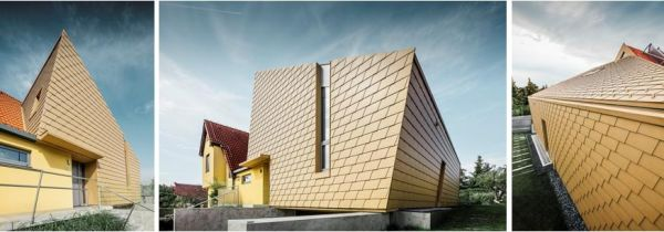 La pelle dorata delle scandole PREFA esalta le forme insolite di una villetta a Praga